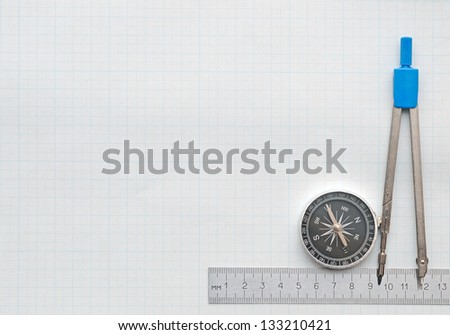 compass and pencil on graph paper - stock photo