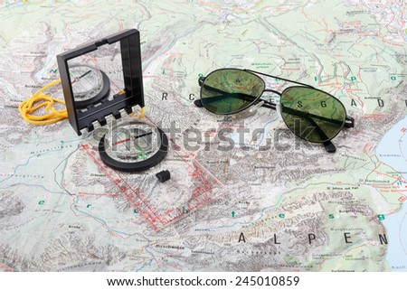 Compass and pilot sunglasses on a hiking map of the Berchtesgaden Alps - stock photo