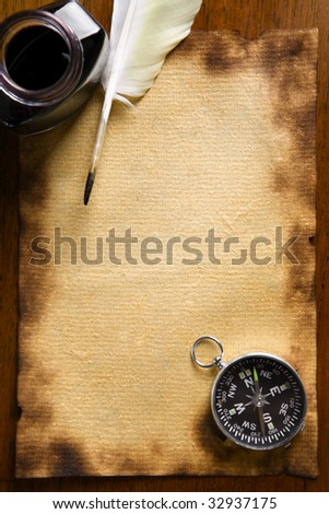 Compass and quill pen on old paper - stock photo