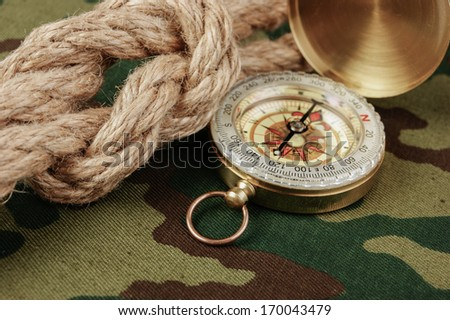 Compass and rope on a camouflage background - stock photo