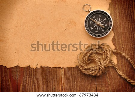 compass and rope on grunge background - stock photo