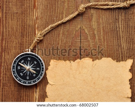 compass and rope on wood background - stock photo