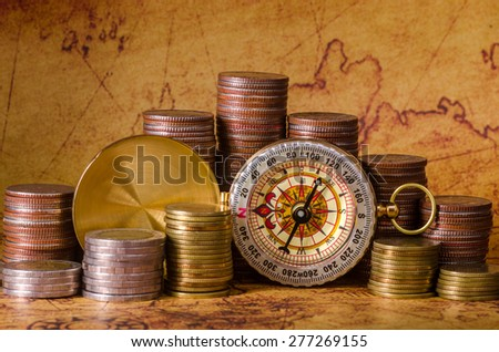 Compass and stack of coins on old map - stock photo