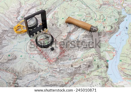 Compass and wooden-handled knife on a hiking map of the Berchtesgaden Alps - stock photo