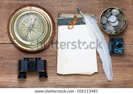 Compass, antique notebook, binoculars, quill and inkwell, coins on wood - stock photo