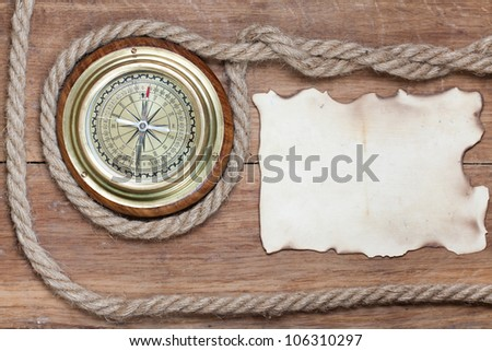Compass, burnt paper, rope on wood