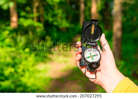 compass in a female hand lost in the woods - stock photo