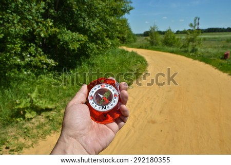 Compass in hand. Magnetic compass is in the hand of the person on a background summer landscape. - stock photo