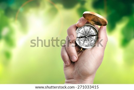 Compass in hand on natural background - stock photo