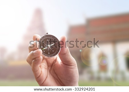 compass in hand on thai temple blur background with lighting flare