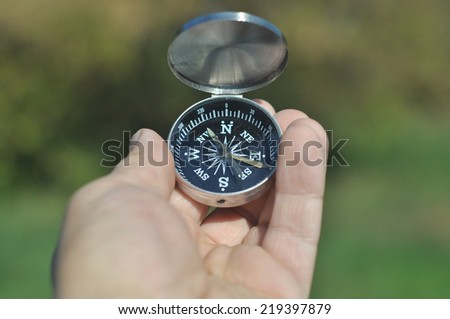 Compass in hand. Open the magnetic compass holds the left hand men. - stock photo