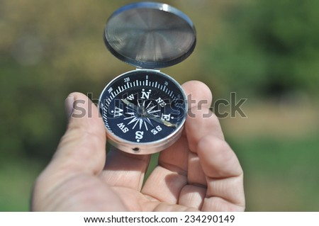 Compass in hand. The magnetic compass lies in a man's hand on a background of nature. - stock photo