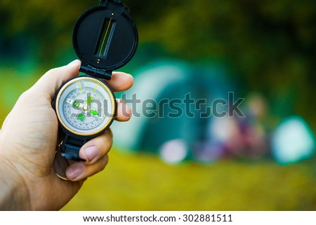 Compass in hand traveler on green background