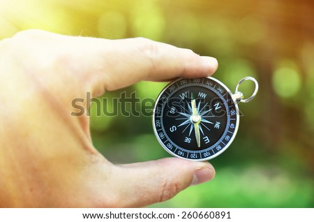 Compass in the hand against against wood - stock photo