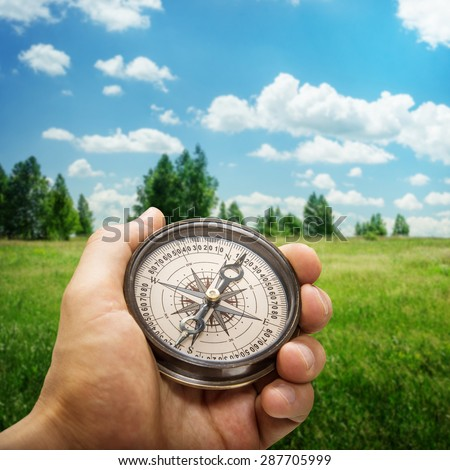 Compass in the hand against rural road - stock photo
