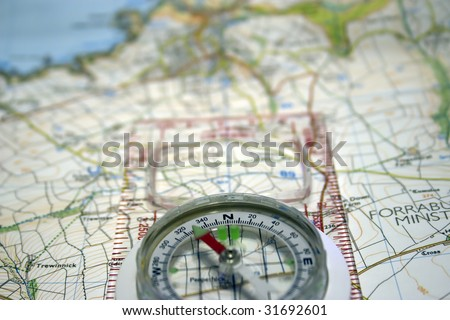 Compass laid on top of map - stock photo