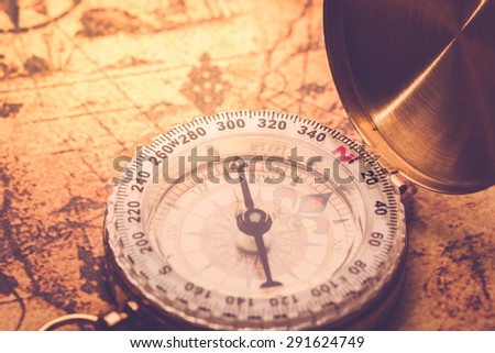 compass lying on vintage map. - stock photo