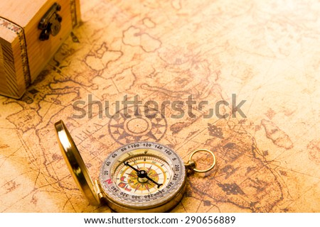 compass lying on vintage map with treasure chest  - stock photo
