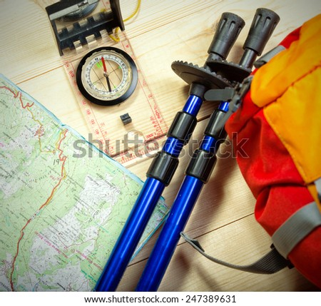 compass, map, trekking poles and backpack on a wooden background - stock photo