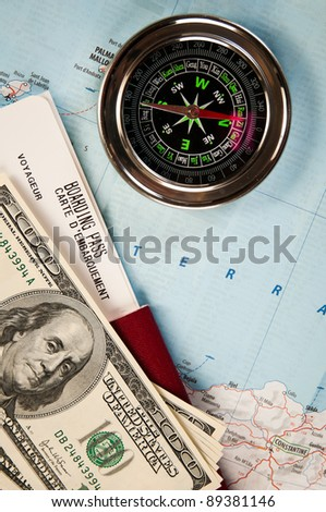 compass, money and passport with boarding pass - stock photo
