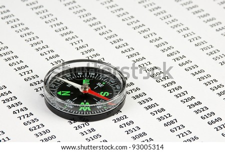 compass on a document with columns of figures - stock photo