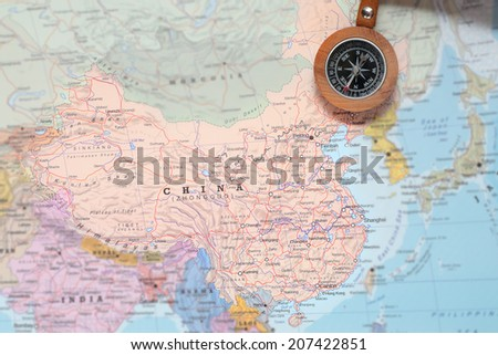 Compass on a map pointing at China and planning a travel destination - stock photo