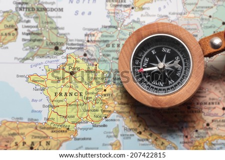Compass on a map pointing at France and planning a travel destination - stock photo