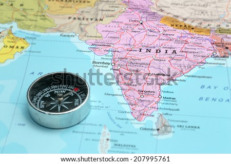 Compass on a map pointing at India and planning a travel destination - stock photo