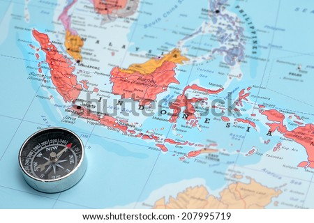 Compass on a map pointing at Indonesia and planning a travel destination - stock photo