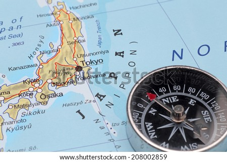 Compass on a map pointing at Japan and planning a travel with destination Tokyo - stock photo