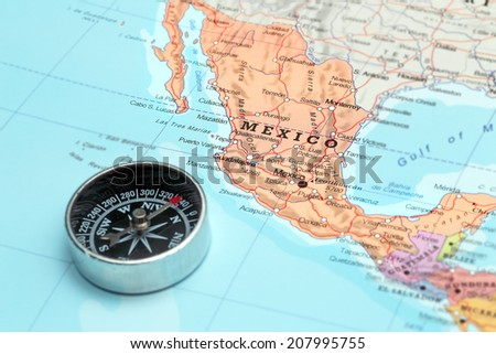 Compass on a map pointing at Mexico and planning a travel destination - stock photo