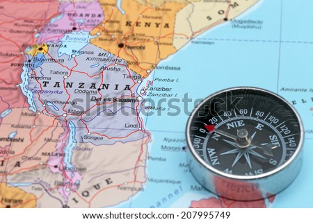 Compass on a map pointing at Tanzania and planning a travel destination - stock photo