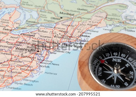 Compass on a map pointing at United States and planning a travel with destination New York - stock photo