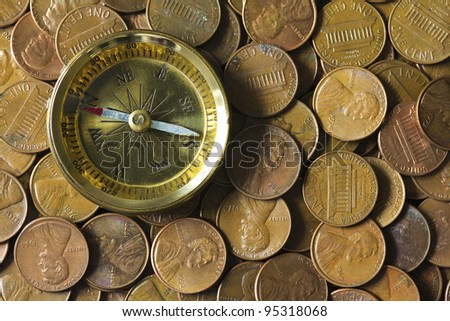 Compass on a pile of American pennies representing finance and economy directions. - stock photo