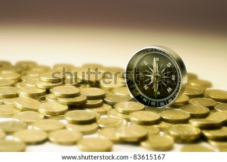 Compass on Coins in Warm Tone - stock photo