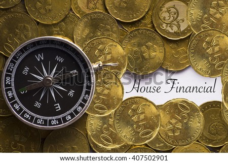 """Compass on Coins with """"House Financial"""" text on copy space - financial direction and business concept - stock photo"""