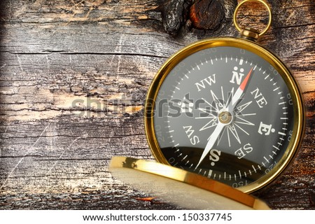 Compass on cracked wooden background - stock photo