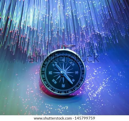 Compass on fiber optic background - stock photo