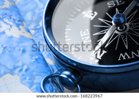 Compass on map background in blue toning