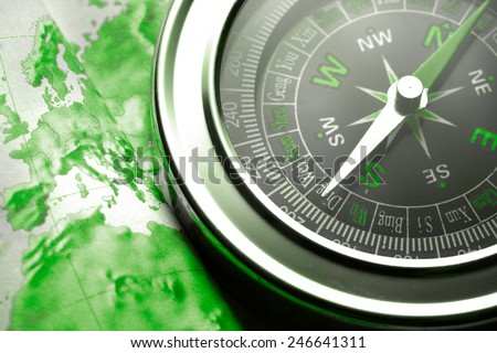 Compass on map background in green toning