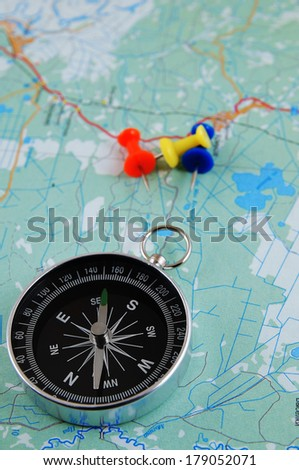 Compass on map with push pins  - stock photo