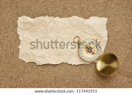 Compass on old sheet crumpled paper against the background of sand - stock photo