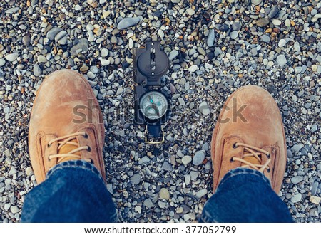 Compass on pebble coastline near legs of hiker man outdoor. Point of view shot. Theme of hiking and travel - stock photo