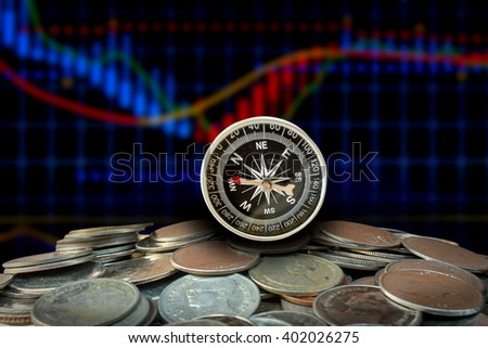 compass on stack coins over blurred of stock chart background. investment, economic map  concept. - stock photo