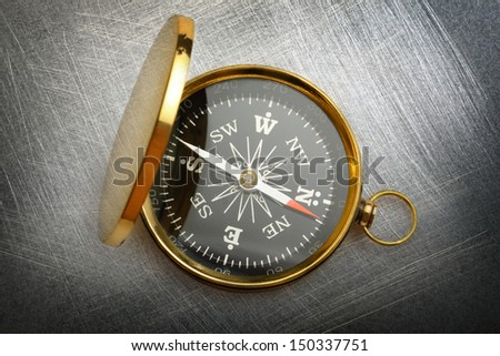 Compass on steel scratchy background - stock photo