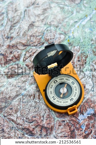 Compass on the map. Magnetic compass in the expanded form is situated on a topographic map. - stock photo