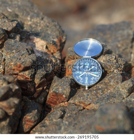 Compass on the rocks - stock photo