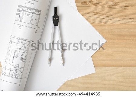 Compass on white paper in top view with copy space. Workplace of architect, constructor, designer. Start a new project. Construction and architecture. Tools for drawing.