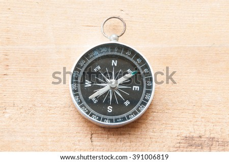 Compass on wooden table. - stock photo