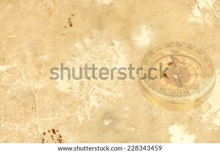 compass over old paper background - stock photo